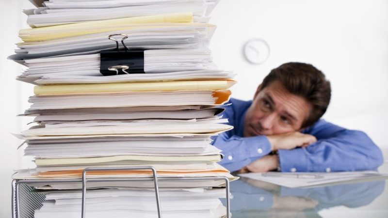 Man overwhelmed with insurance paperwork