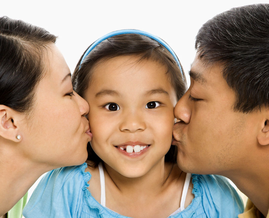 smiling girl with parents kissing her cheek