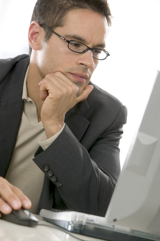 Man with glasses looking at computer screen