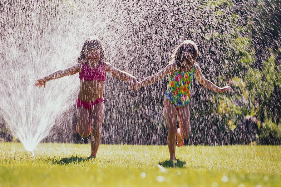 girls in swimsuits running through the sprinkler on the grass