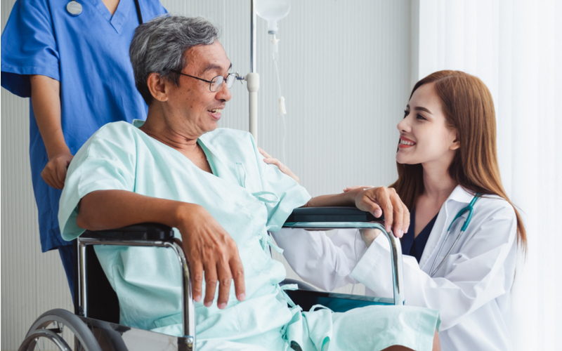empathetic doctor with patient in wheelchair