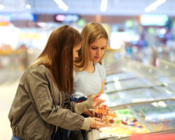 young women shopping and inspecting food labels in freezer section