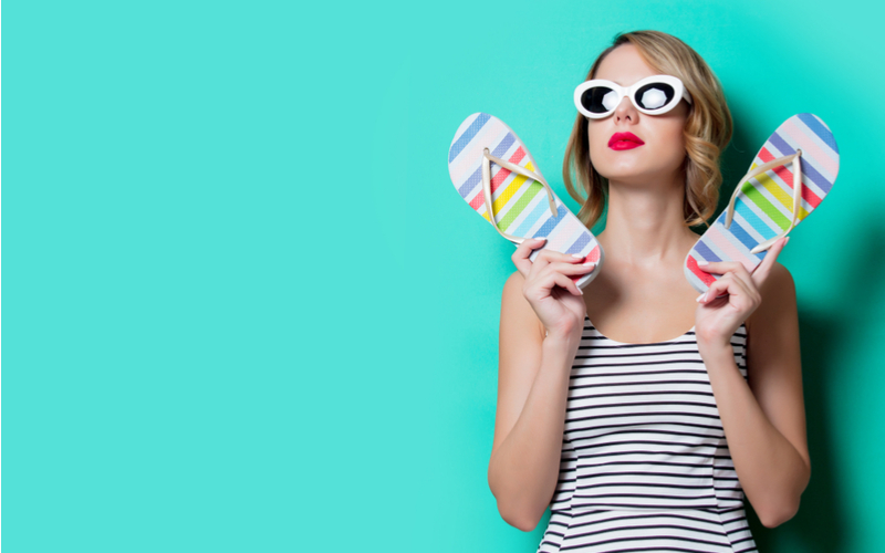 woman with sunglasses and striped tank top holding flip flops on turquoise background