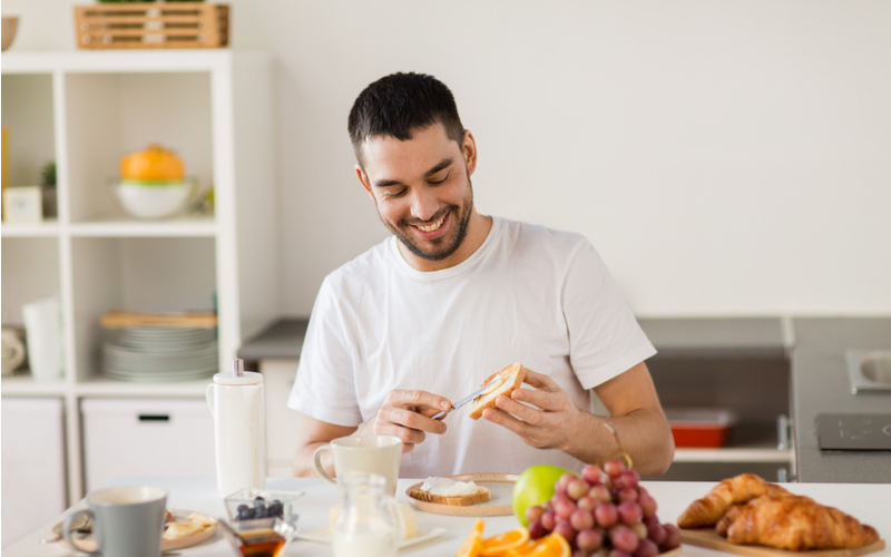 man in kitchen spreading cheese on bread and eating fruit and drinking hot tea