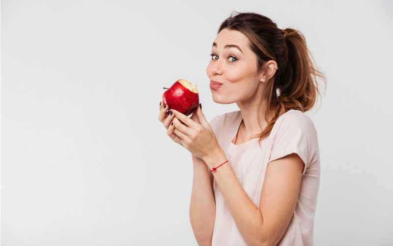 young woman with brunette ponytail eating apple