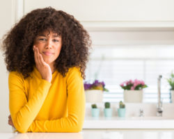 Young Black Woman in Yellow Sweater in Kitchen Touching Cheek with Dental Pain