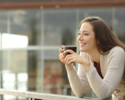 Smiling young professional woman with long hair drinking coffee on balcony