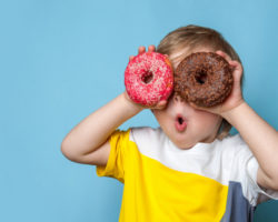 Playful Little Boy Holding Donuts Over Eyes