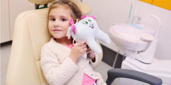Little Girl in Dentist Chair Holding Stuffed Tooth