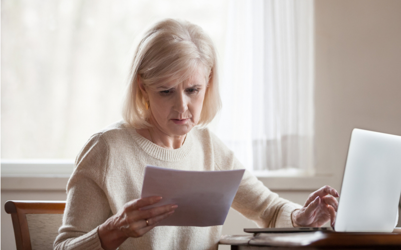 Older Woman Examining Paper at Desk with Laptop
