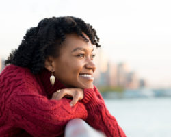 Young Hopeful Black Woman Looking Out Over Bridge and Smiling
