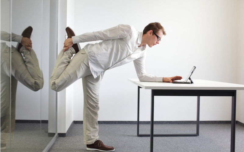 Man Standing and Stretching at Desk While Working On Laptop